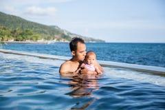 Behandla som ett barn ha gyckel i simbassängen med modern Royaltyfria Bilder