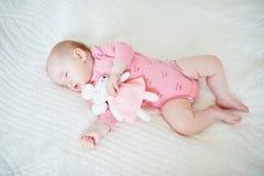 Behandla som ett barn ha ta sig en tupplur med hennes favorit- musleksak fotografering för bildbyråer