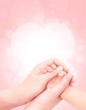 Behandla som ett barn handen i moderhand slappt Arkivbild