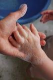 Behandla som ett barn handen med skum Arkivfoton