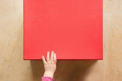 Behandla som ett barn handen som öppnar en gåvaask Arkivfoton