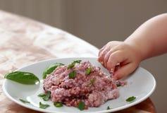 Behandla som ett barn handen som försöker att äta havremjölhavregröt Royaltyfri Foto