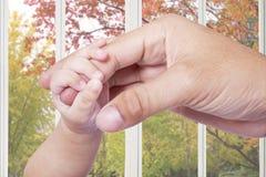 Behandla som ett barn handen som griper faderfingret Arkivfoto