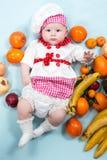 Behandla som ett barn hatten för kocken för kockflickan den bärande med nya frukter. Arkivbilder