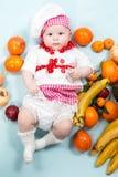 Behandla som ett barn hatten för kocken för kockflickan den bärande med nya frukter Arkivbilder