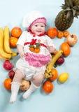 Behandla som ett barn hatten för kocken för kockflickan den bärande med nya frukter Arkivfoto