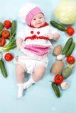 Behandla som ett barn hatten för kocken för kockflickan den bärande med nya grönsaker. Royaltyfria Foton