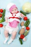 Behandla som ett barn hatten för kocken för kockflickan den bärande med nya grönsaker. Royaltyfri Foto