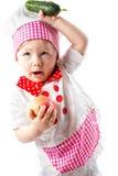 Behandla som ett barn hatten för kocken för kockflickan den bärande med nya grönsaker Royaltyfria Bilder