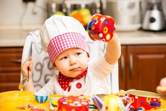 Behandla som ett barn hatten för kocken för kockflickan den bärande med redskap på kök. Arkivbilder