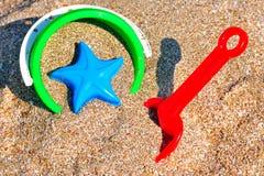 Behandla som ett barn hinken med sand och en skyffel på stranden Royaltyfria Bilder