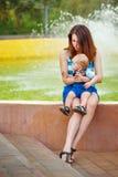 behandla som ett barn holdingmodern Hållande bagel för dotter Arkivfoto