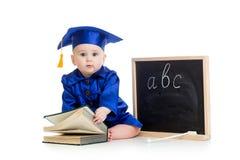 Behandla som ett barn i akademikerkläder med boken och den svart tavlan Royaltyfri Foto