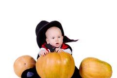 Behandla som ett barn i den svart halloween kappan med pumpa Royaltyfri Bild