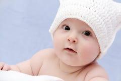 Behandla som ett barn i den vita hatten Arkivfoto