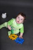 Behandla som ett barn i gröna crawlsimmare som sitter på golv royaltyfria bilder