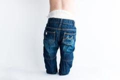 Behandla som ett barn i påsig jeans Royaltyfri Foto