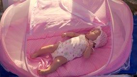 Behandla som ett barn i rosa babylift på stranden stock video