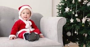 Behandla som ett barn i santa som dräkten sitter på soffan med julgranen stock video