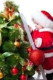 behandla som ett barn jul som dekorerar treen Arkivfoto