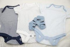 Behandla som ett barn kläderbodysuits, och sockor för nyfött behandla som ett barn royaltyfri bild
