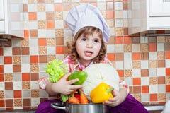Behandla som ett barn kocken med grönsaker Royaltyfria Bilder