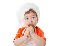 Behandla som ett barn kocken som äter kakapop som isoleras på vit bakgrund Royaltyfria Bilder
