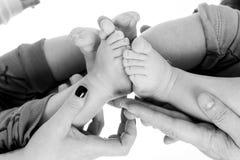 Behandla som ett barn kopplar samman fot i förälderhänder Arkivfoton