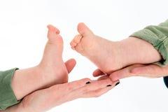 Behandla som ett barn kopplar samman fot i förälderhänder Arkivbild