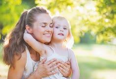 Behandla som ett barn krama modern utomhus Royaltyfria Foton
