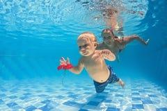 Behandla som ett barn kursen för undervattens- simning med instruktören i pölen Royaltyfri Bild