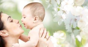 Behandla som ett barn kyssande förtjusande för lycklig moder Arkivbild
