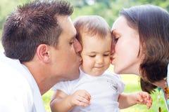 behandla som ett barn kyssande föräldrar Arkivbild