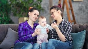 Behandla som ett barn le förtjusande ung moder som två tycker om moderskap som spelar med lite gulligt, på det hemtrevliga hemmet