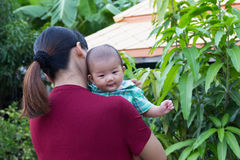 Behandla som ett barn leendet lyckligt med innehavhandmodern i trädgården Arkivbilder