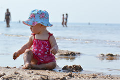 Behandla som ett barn lek med sand på havet royaltyfria foton
