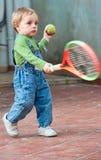 behandla som ett barn leka tennis för pojken Arkivbilder