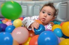 Behandla som ett barn lekar med färgrika bollar Arkivfoton