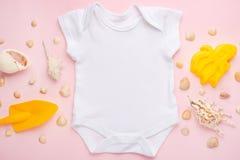 Behandla som ett barn lekmanna- vit för modelllägenheten bodysuitskjortan på en rosa bakgrund med ett nautiskt tema, skal och hav royaltyfri fotografi