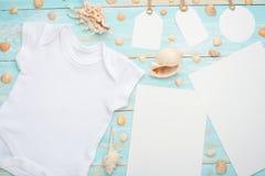 Behandla som ett barn lekmanna- vit för modelllägenheten papper och etiketter för skjortabodysuitmodell för design på en blå träb fotografering för bildbyråer
