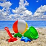 Behandla som ett barn leksaker på strandsand Arkivfoto