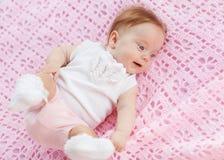 Behandla som ett barn ligger på en rosa handduk. Arkivfoton