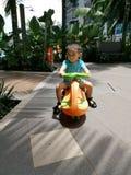 Behandla som ett barn lilla barnet som rider en sparkcykel royaltyfri foto