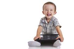 Behandla som ett barn lilla barnet som ler och rymmer en digital minnestavla Arkivfoto