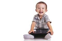 Behandla som ett barn lilla barnet som smilling och rymmer en digital minnestavla Arkivfoton