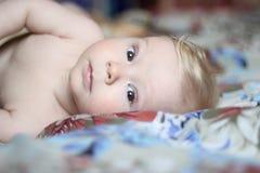 Behandla som ett barn lite att ligga på den härliga sängkläderna Arkivfoto