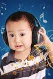 Behandla som ett barn lite att lyssna till musik Arkivfoto