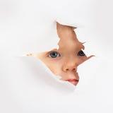 Behandla som ett barn lite att se ut ur ett hål Royaltyfria Foton