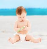 Behandla som ett barn lite att spela med tandborsten Arkivbild