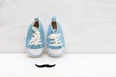 Behandla som ett barn lite blåttgymnastikskor och mustascher på en vit träbackgr Fotografering för Bildbyråer